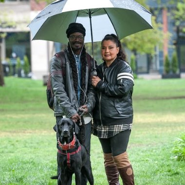 A couple who met at the 24/7 respite centre enjoying a rainy day at the Moss park with their black labrador dog. Your donations help people move into housing.