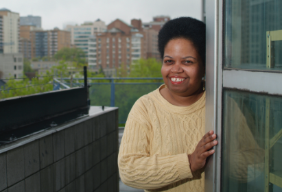 Afro Canadian woman smiling from her affordable housing unit at 145 queen Street East
