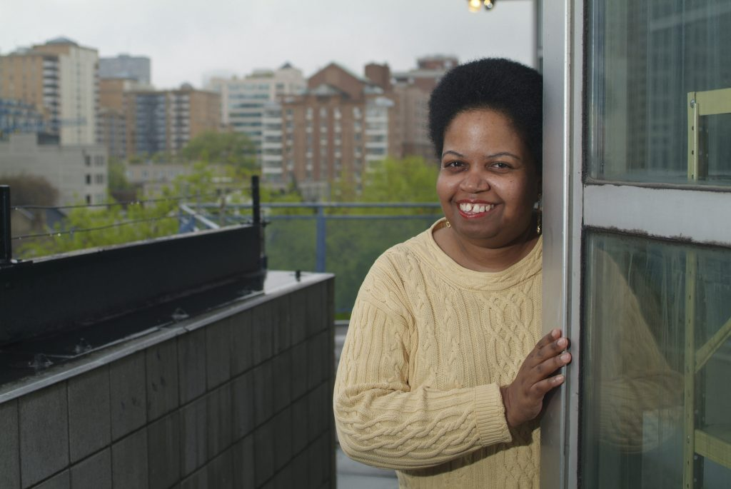 Woman smiling from her affordable housing unit at 145 queen Street East