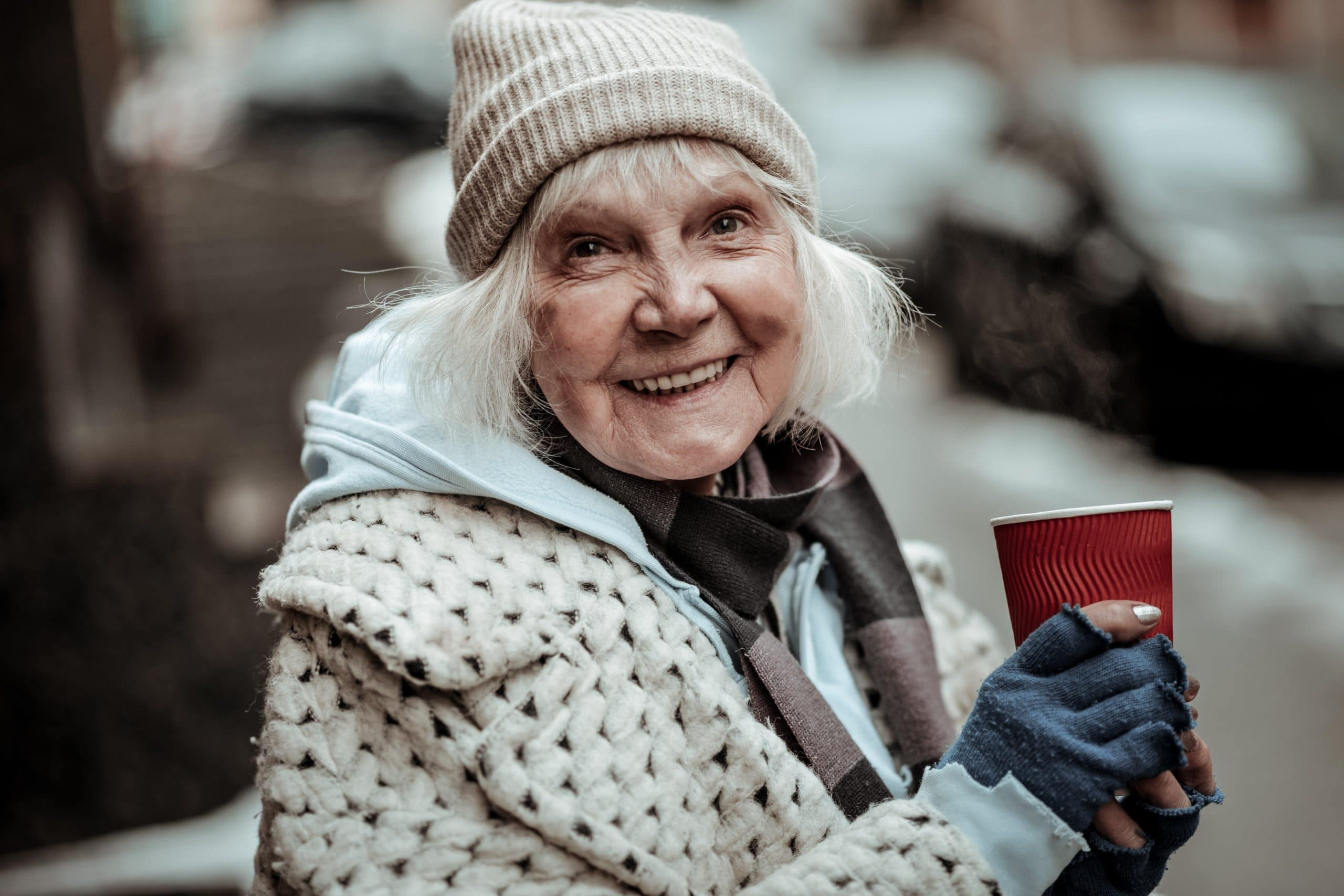 Homeless lady enjoying a warm beverage