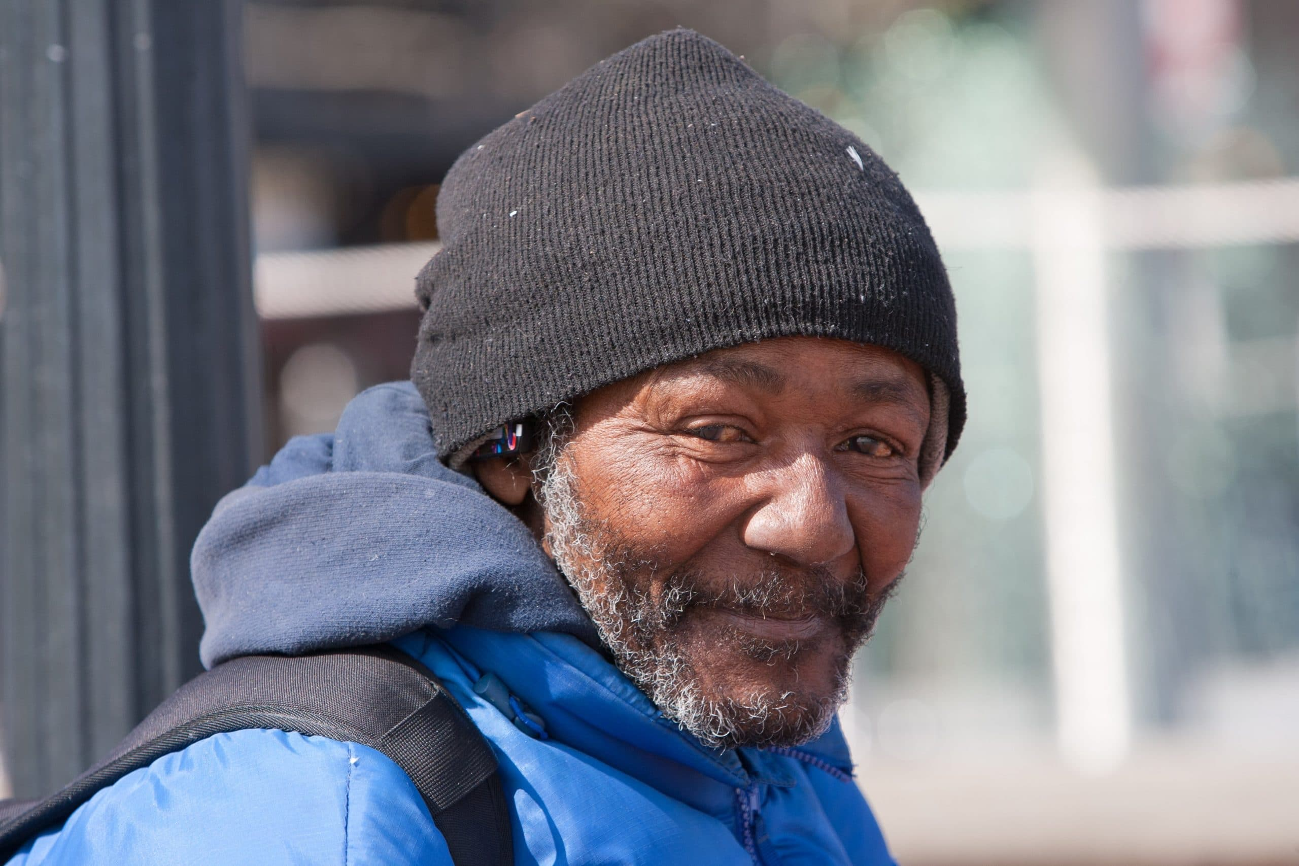 Homeless man wearing a hat and smiling to the camera