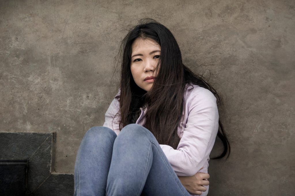 Young woman sitting outdoors and dealing with pain