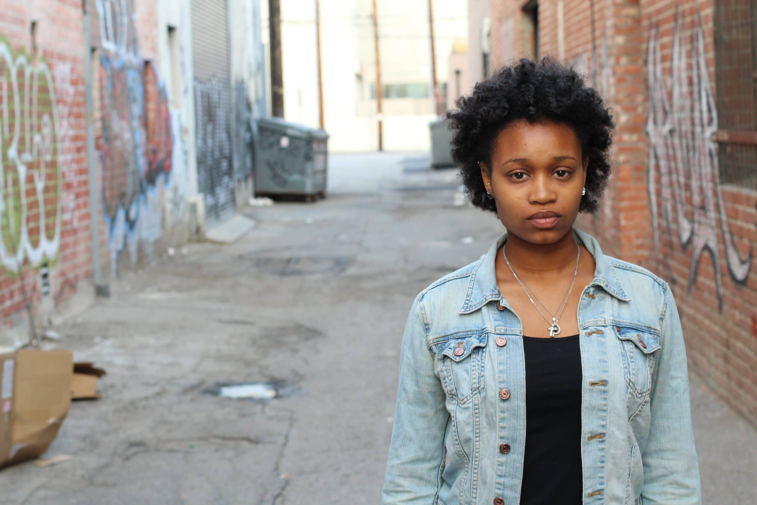 Afro american woman standing in the alley