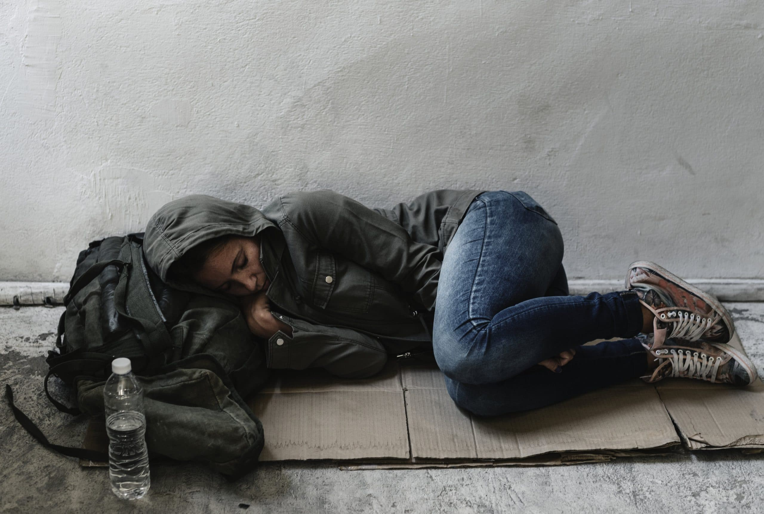 Homeless woman sleeping on a cardboard mat