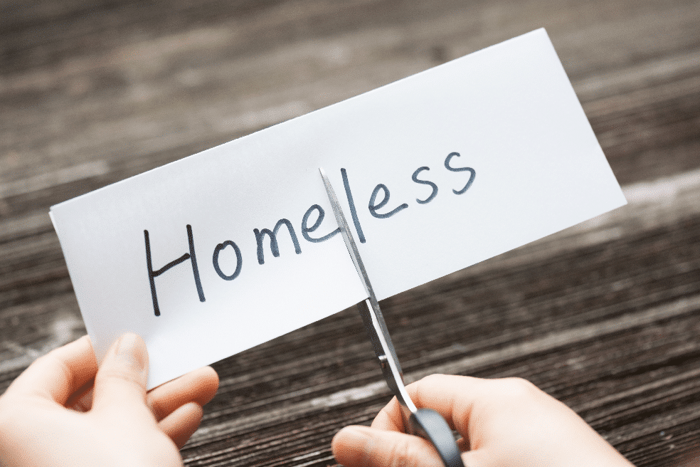 Scissors cutting slip of a paper that says homelessness on it
