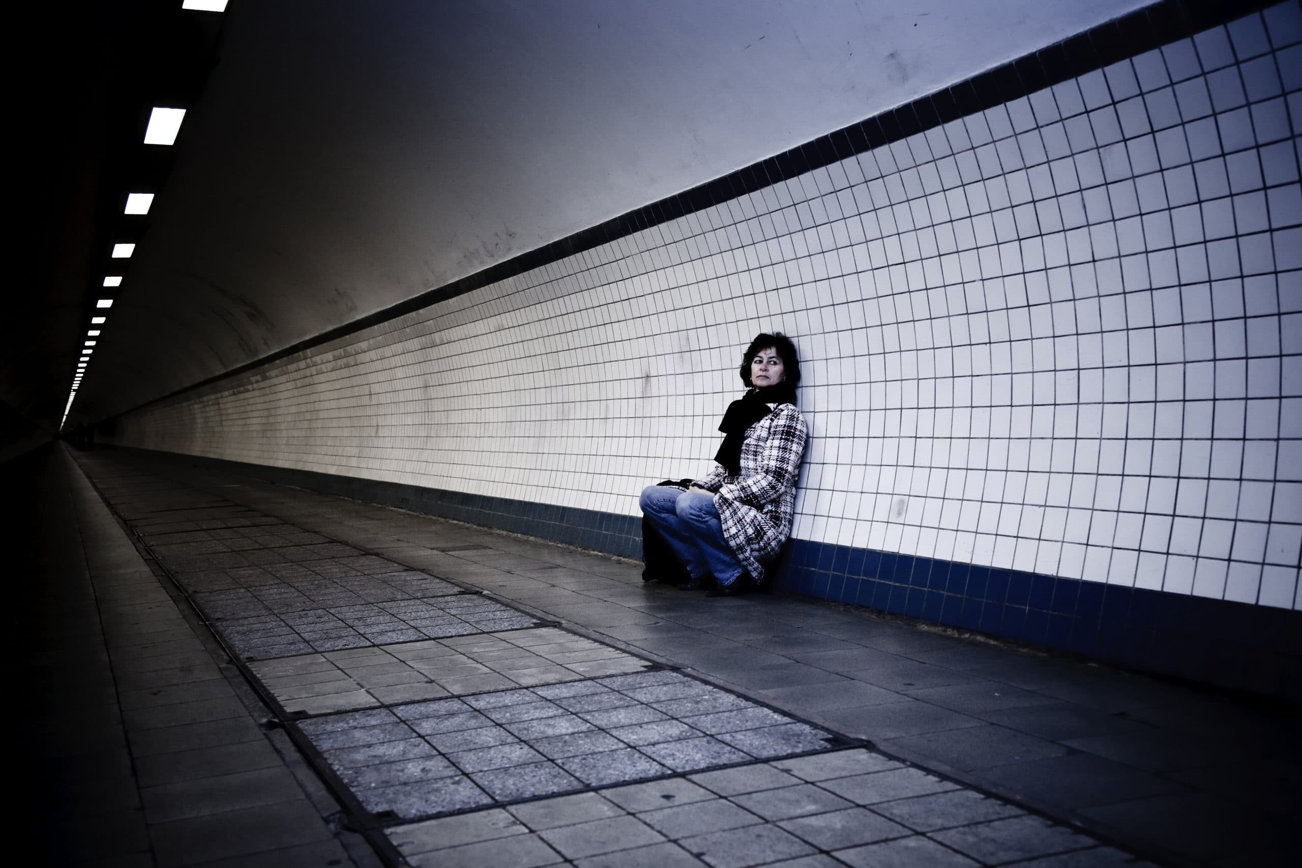 Woman leaning against the wall on empty subway platform