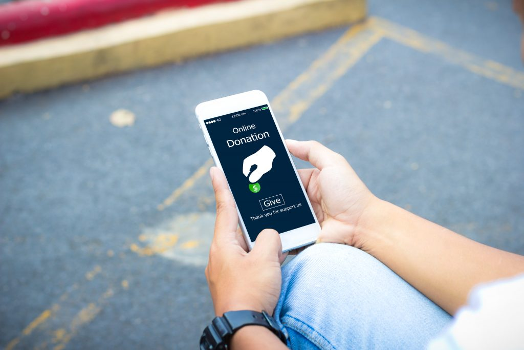 A person is making a donation to charity via smartphone