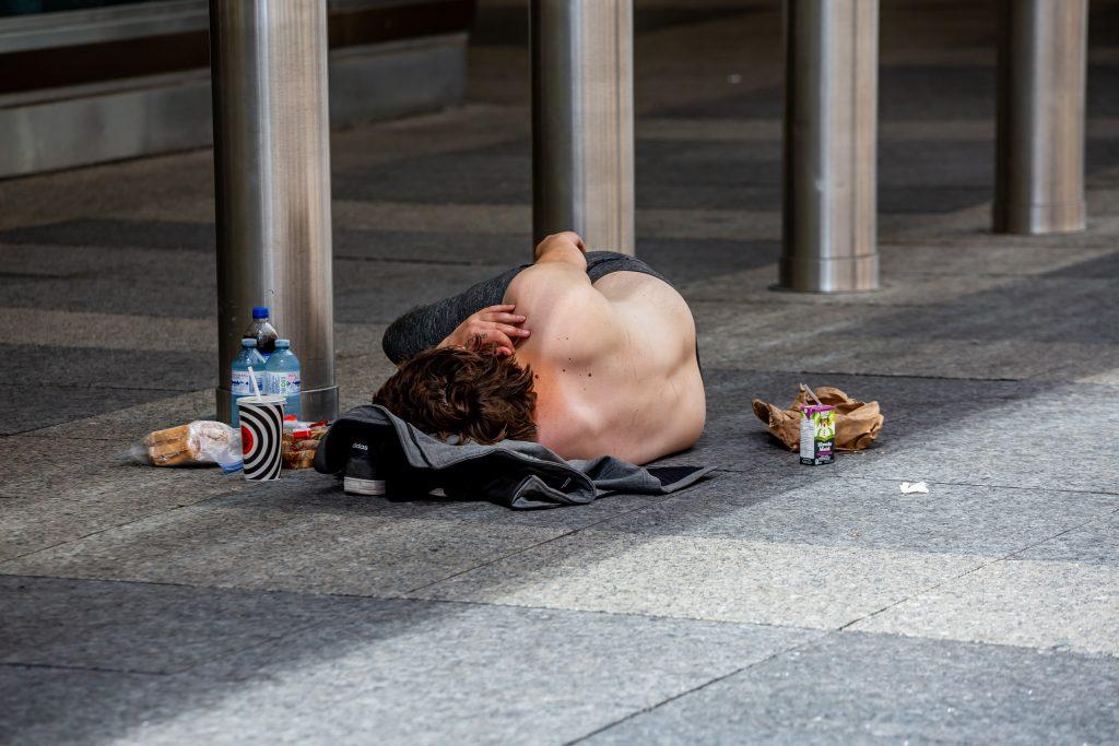 Homeless man sleeping outdoors on a hot summer day