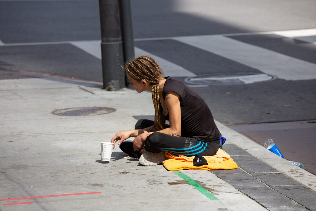 Young homeless woman sitting on the street in Toronto