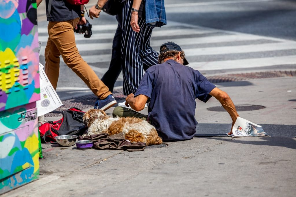 Homeless Man and his dog sitting while others are walking by