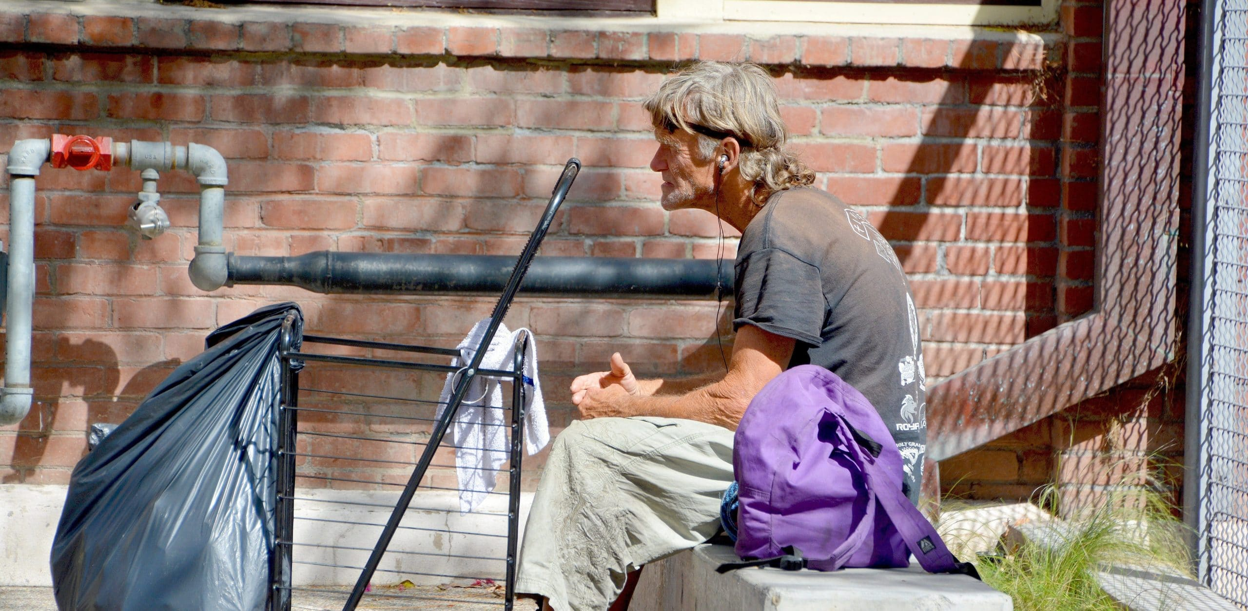 Homeless man sitting in a hot summer day