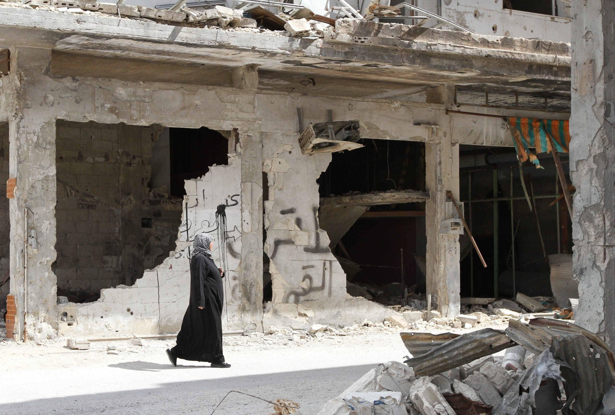A woman walks near a house in the city of Homs destroyed in the fighting between the rebels of the Syrian National Army  A
