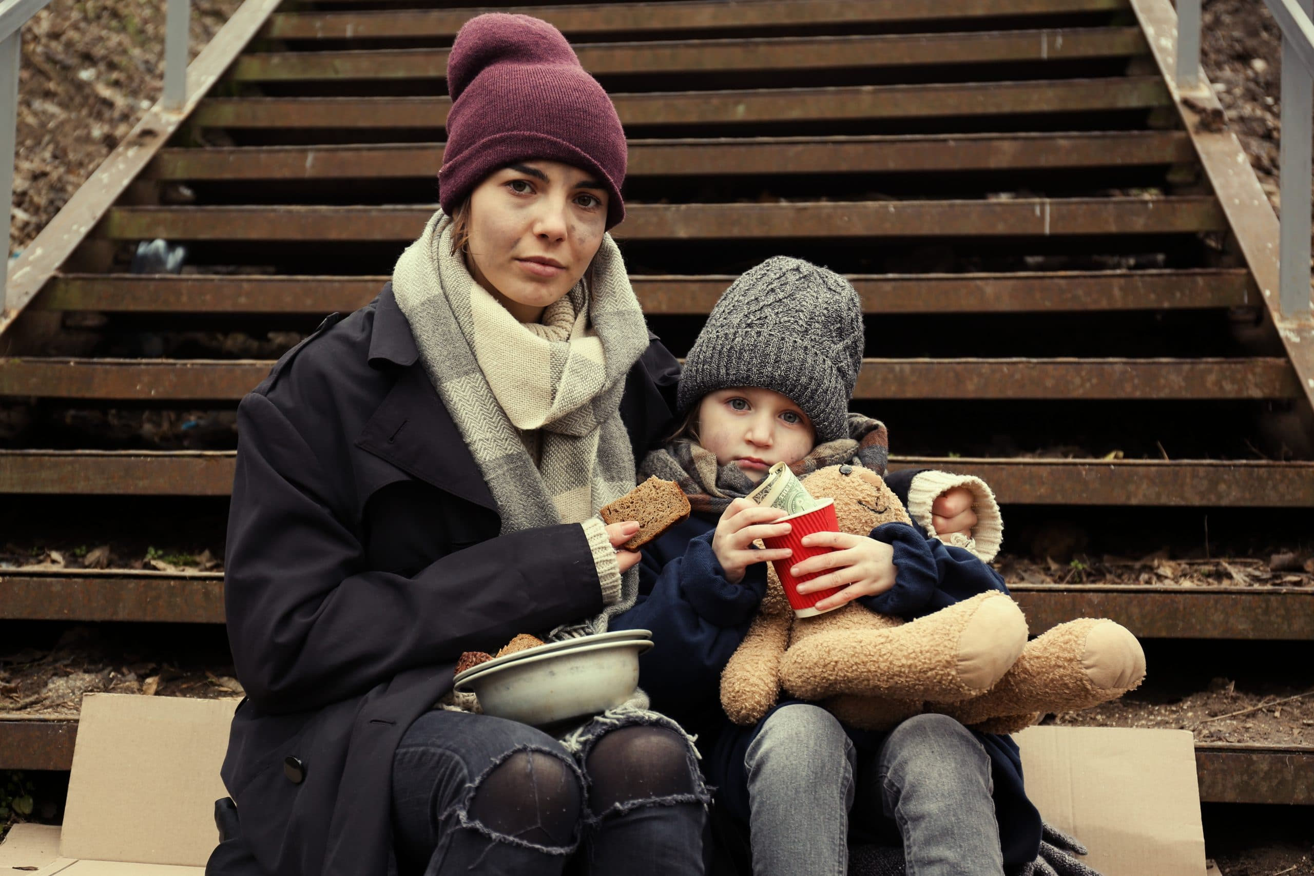 Poor mother and daughter with bread sitting on stairs outdoors  N