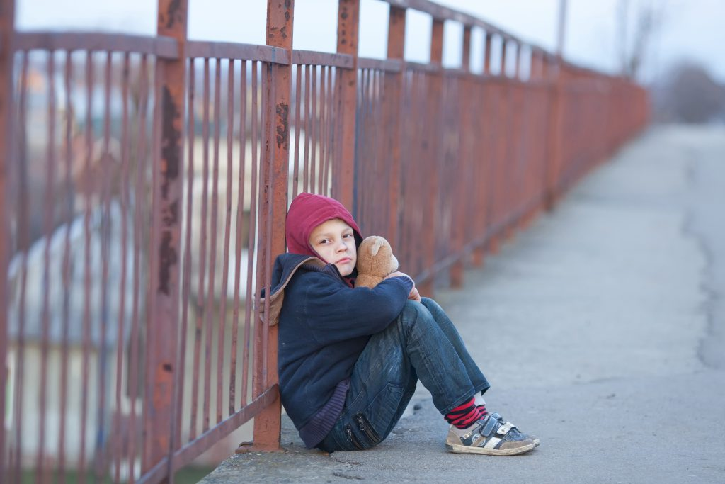 Young boy sitting out doors and holding a teddy bear.