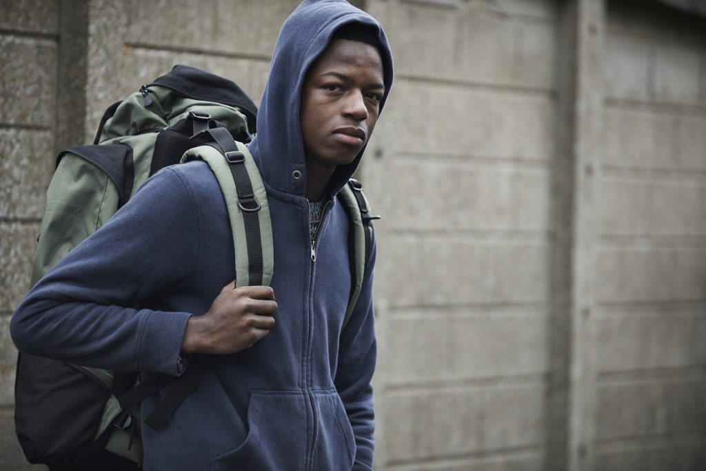 Young, black male with a backpack with all his belongings.