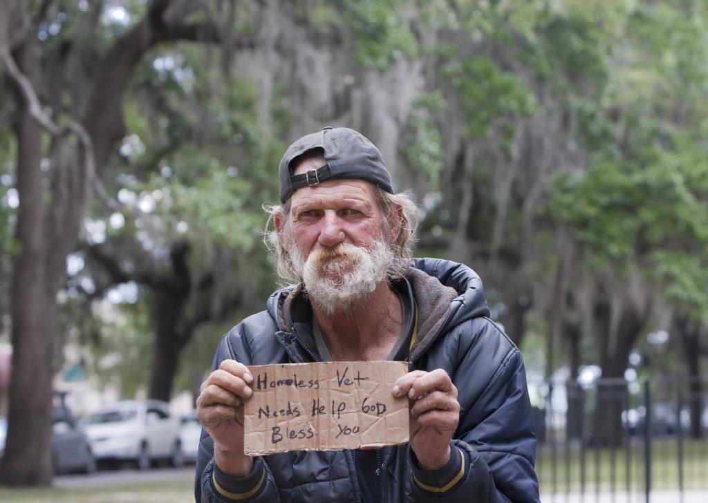 A homeless veteran holds a sign.
