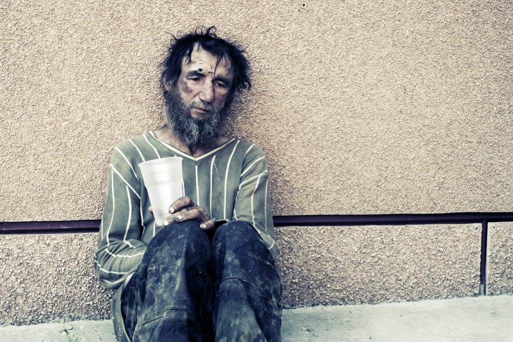 A homeless man is sad and sitting on the street and holding a cup