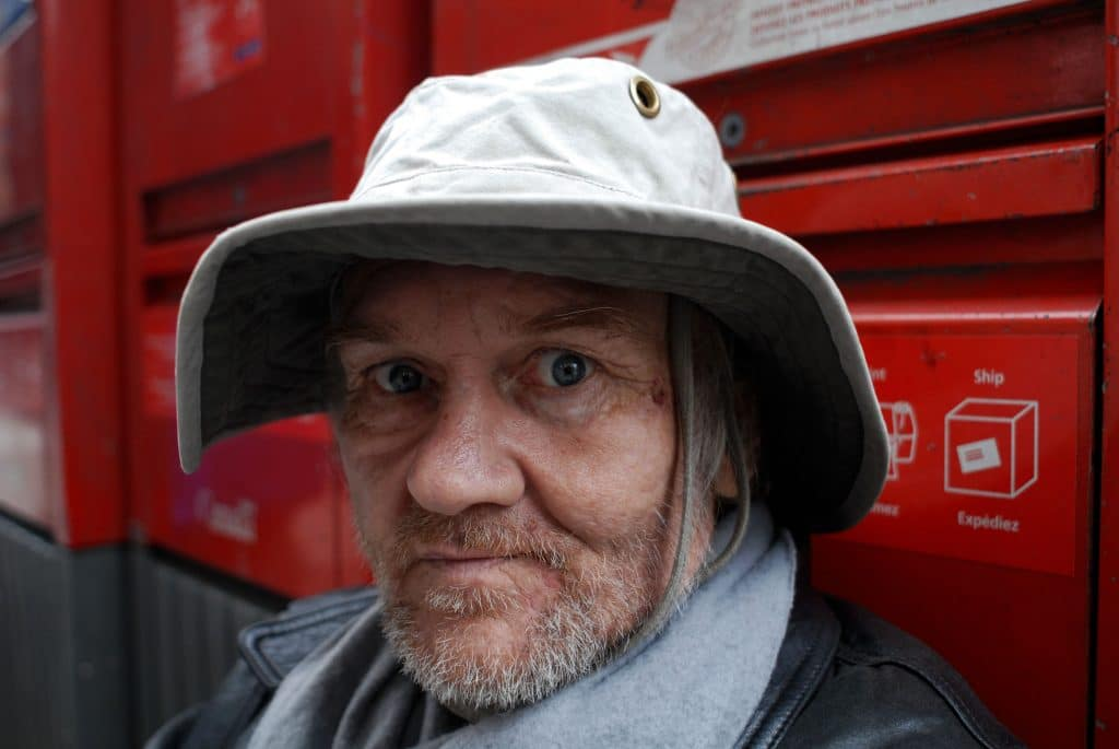 A homeless man is sitting and leaning against street mailbox