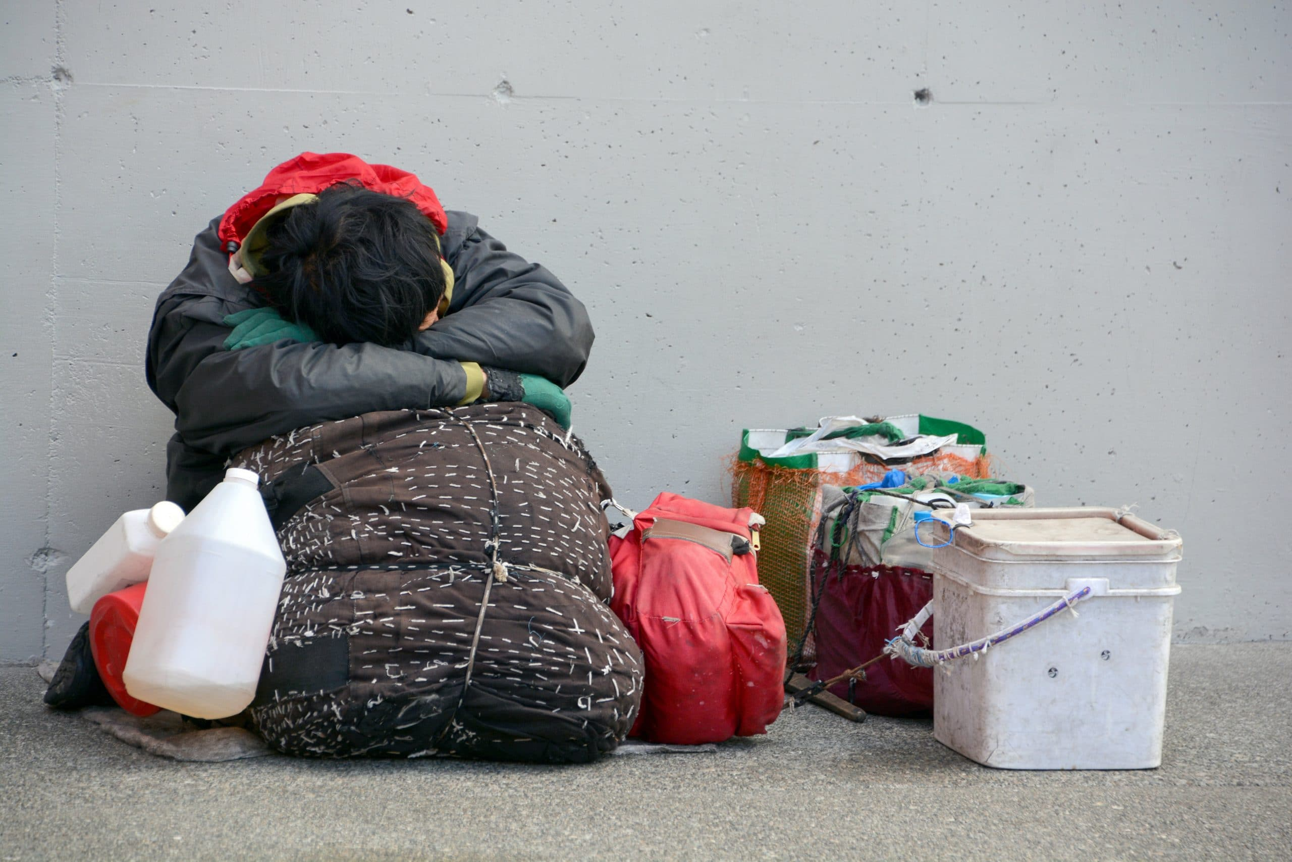 A homeless person sitting on the street wrapped in sleeping bag