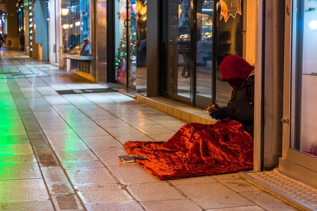 Homeless person sitting on the  Street Near A Window Of A Shop During A Cold Day In The Christmas Period