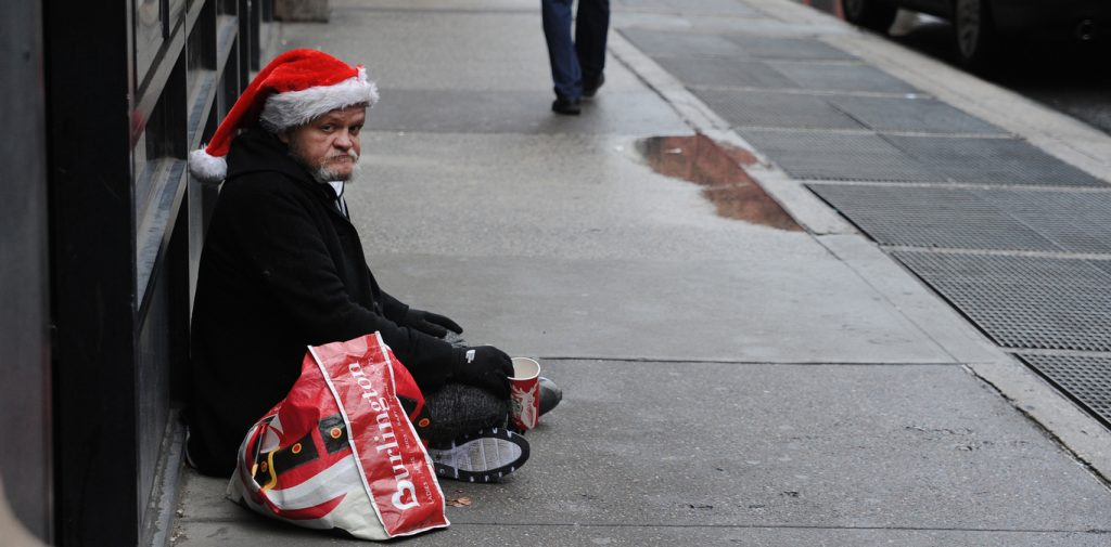 A homeless man wearing a Santa hat asks for help while sitting on the street.