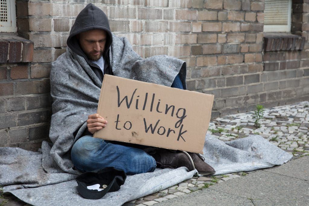 Homeless man sitting outside and holding a sign