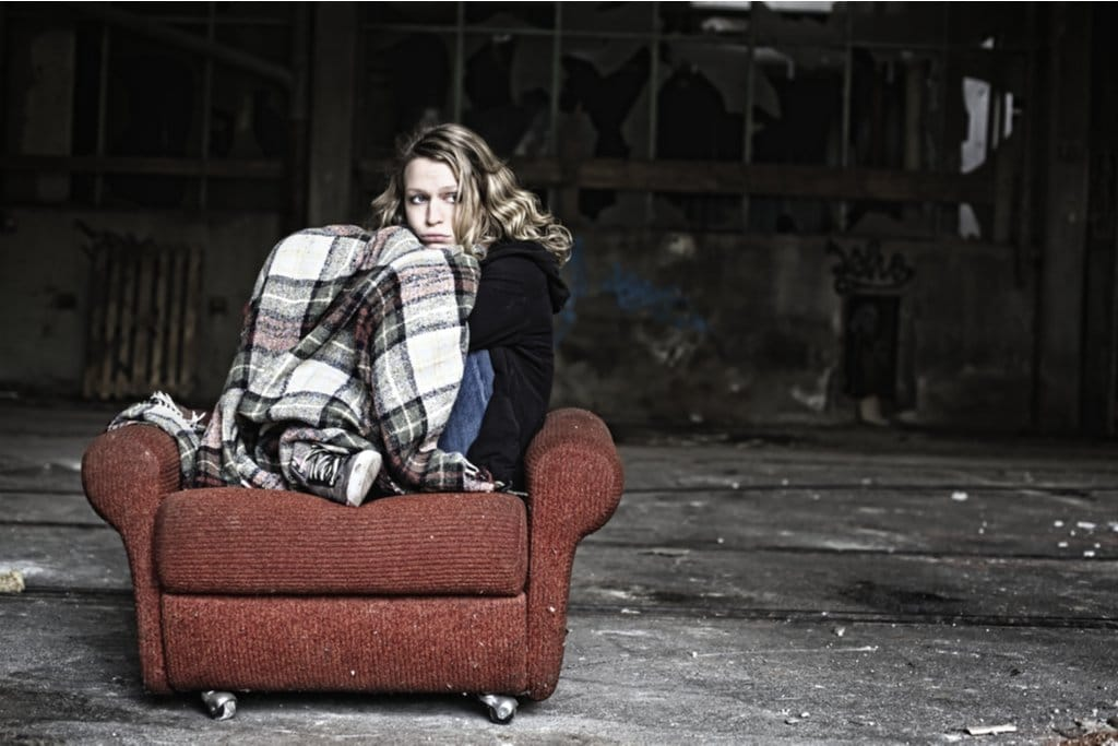 homeless girl sitting on a chair and feeling scared