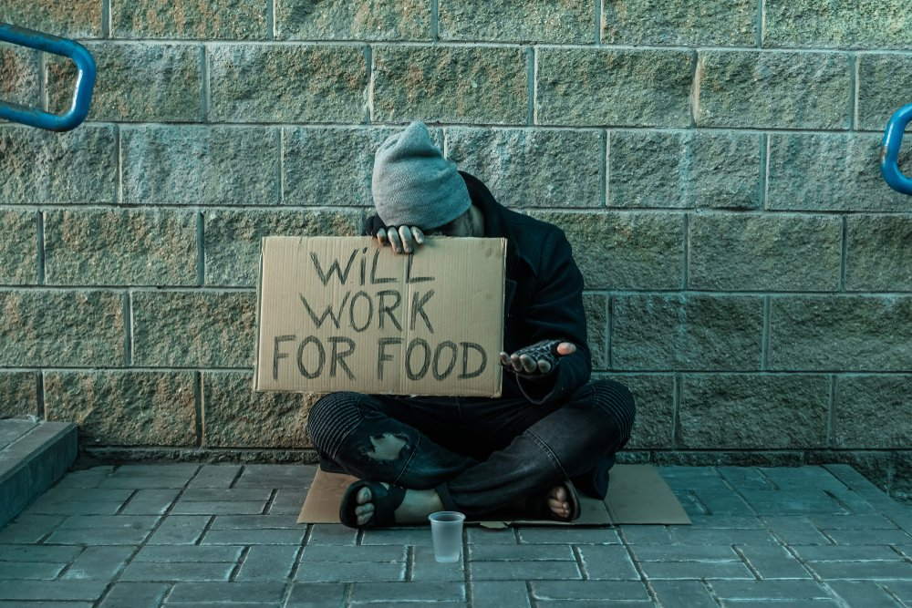 Homeless man sitting and holding a sign