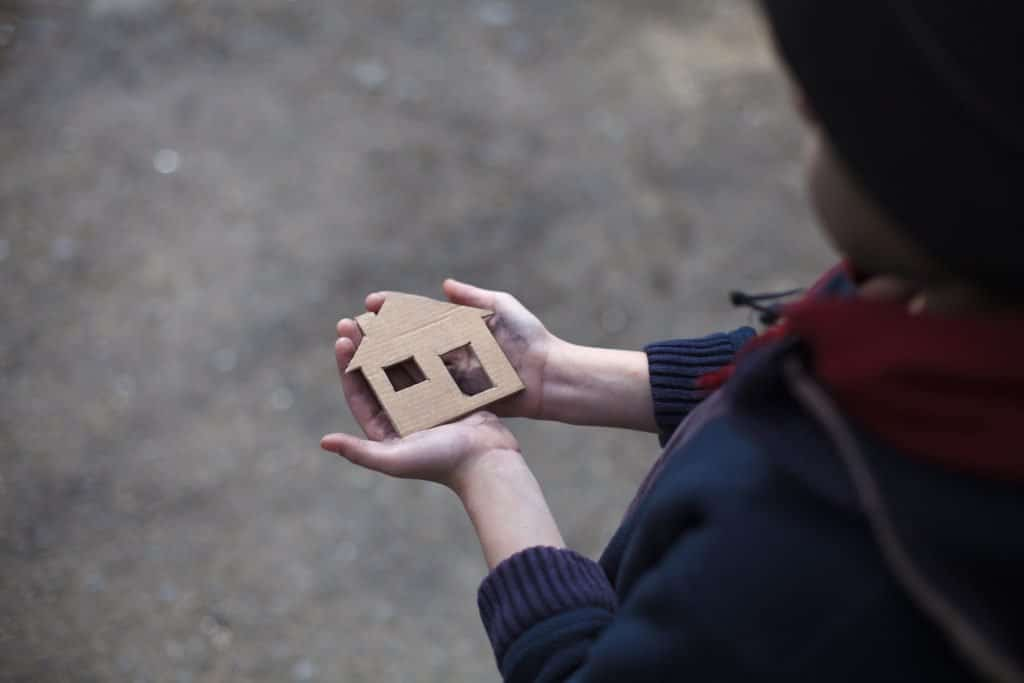 Young homeless person is holding a house shaped cardboard sign representing the need for affordable housing