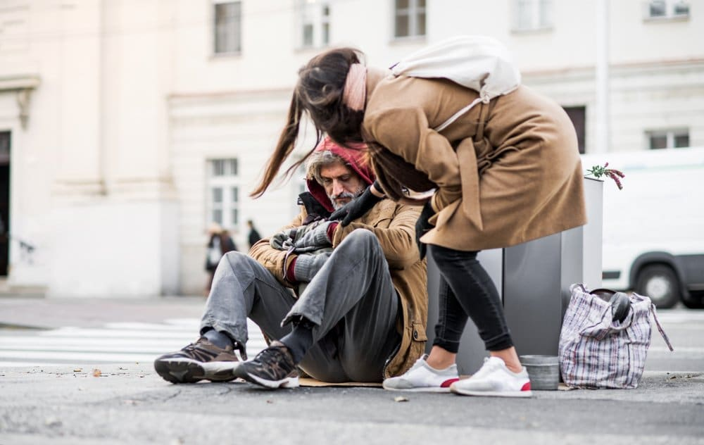 Young woman is helping a homeless man on the street