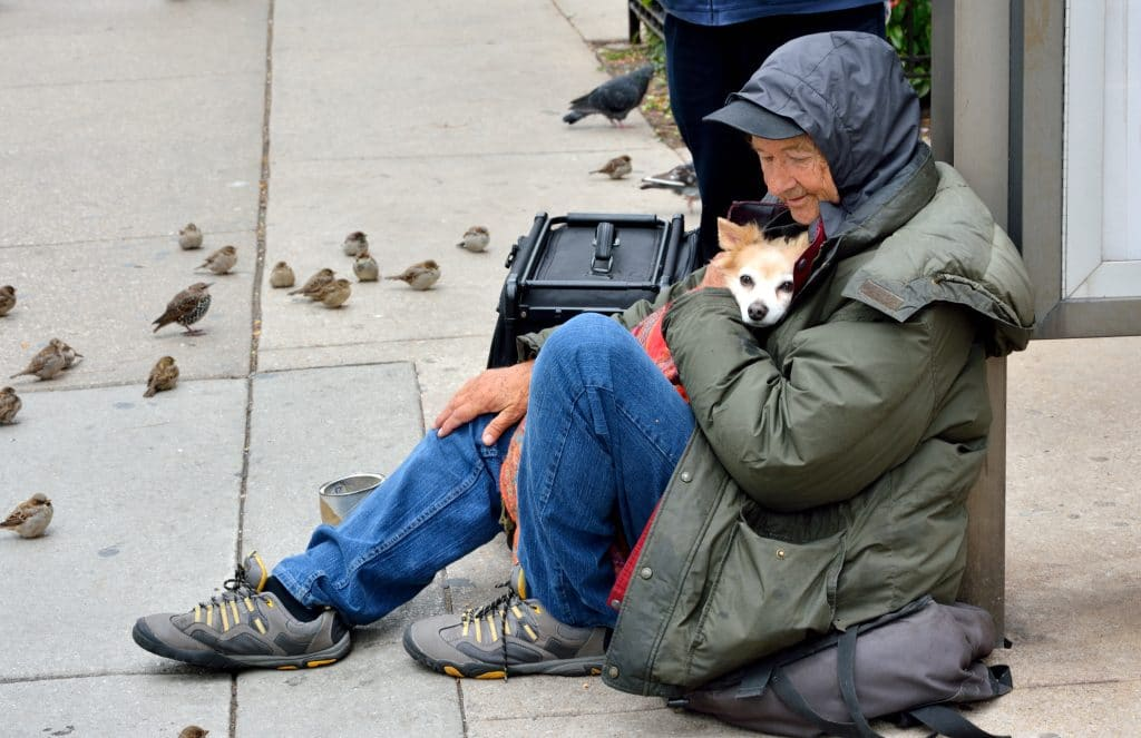 A homeless senior man is cuddling his little cute puppy in his coat