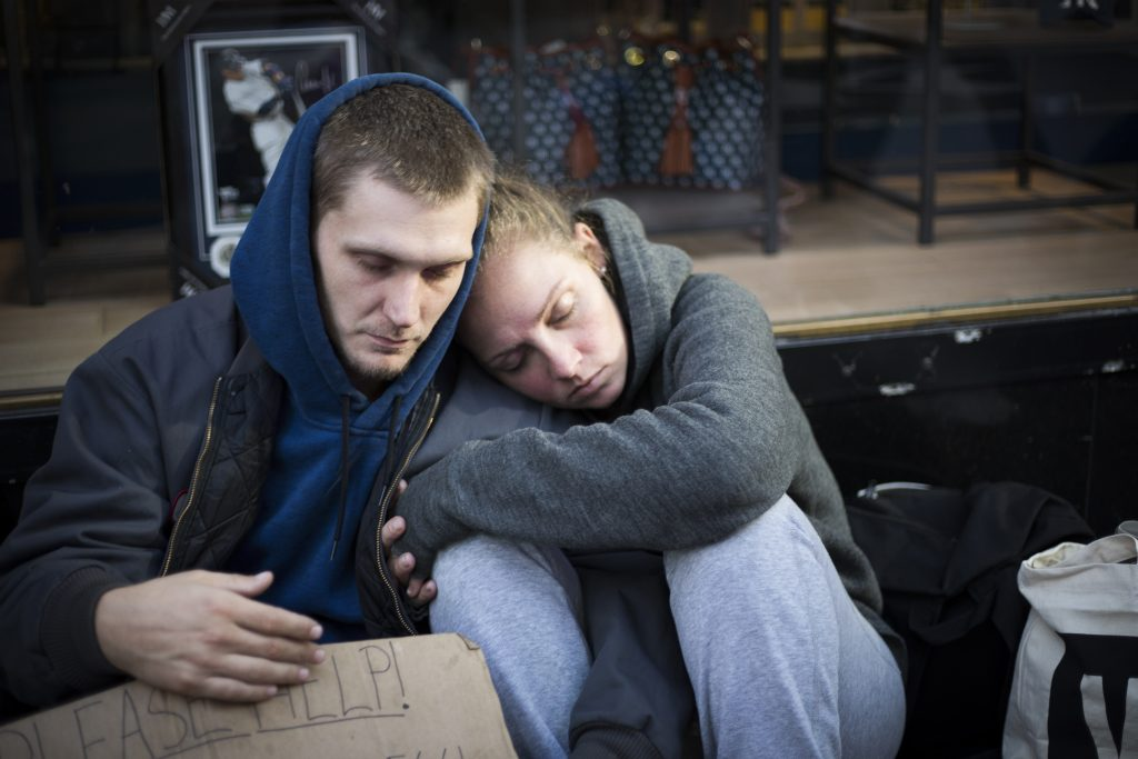 Young homeless couple leeping in the middle of the street