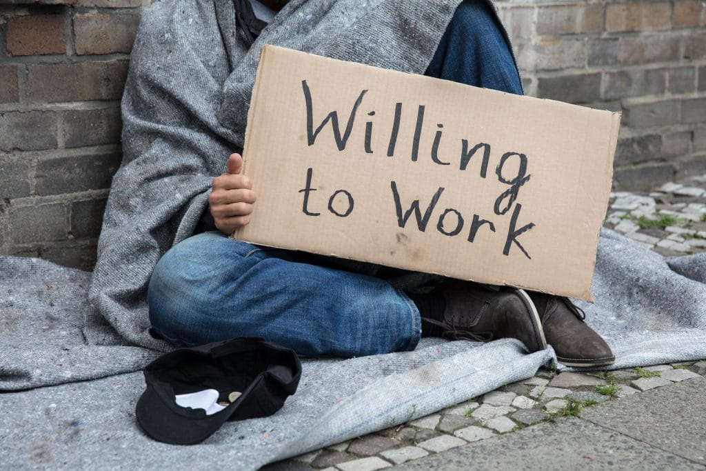 Homeless man holding a sign that says willing to work