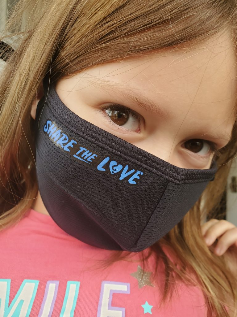 A child is wearing Share The Love mask by Fred Victor