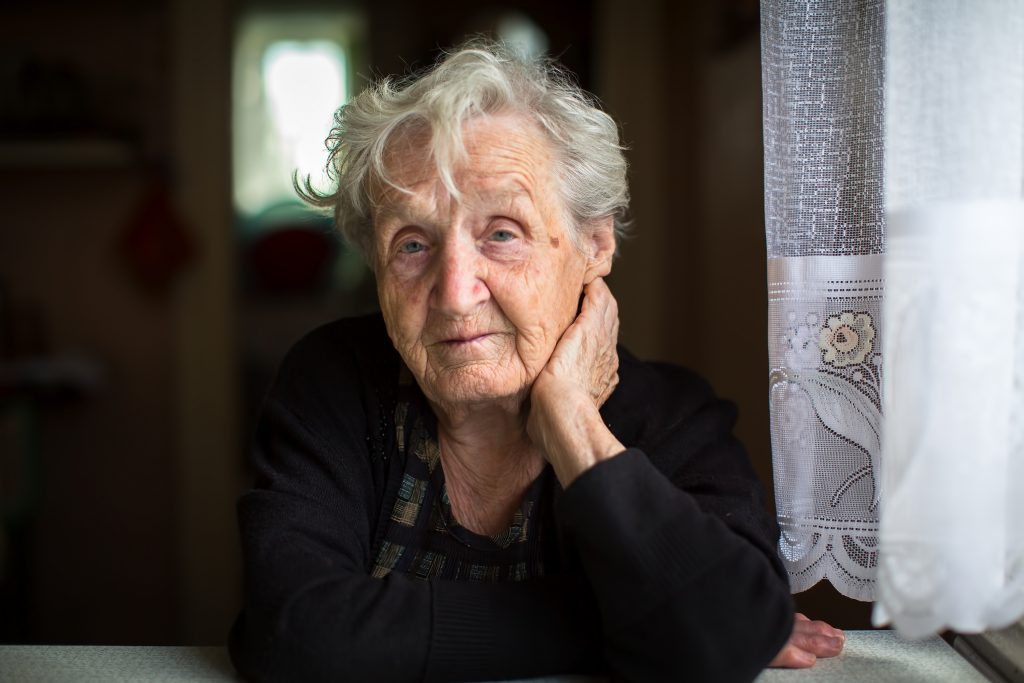 A portrait of an older women sitting at the table