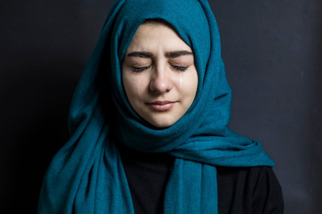 Portrait of a Muslim girl with tears in her eyes.
