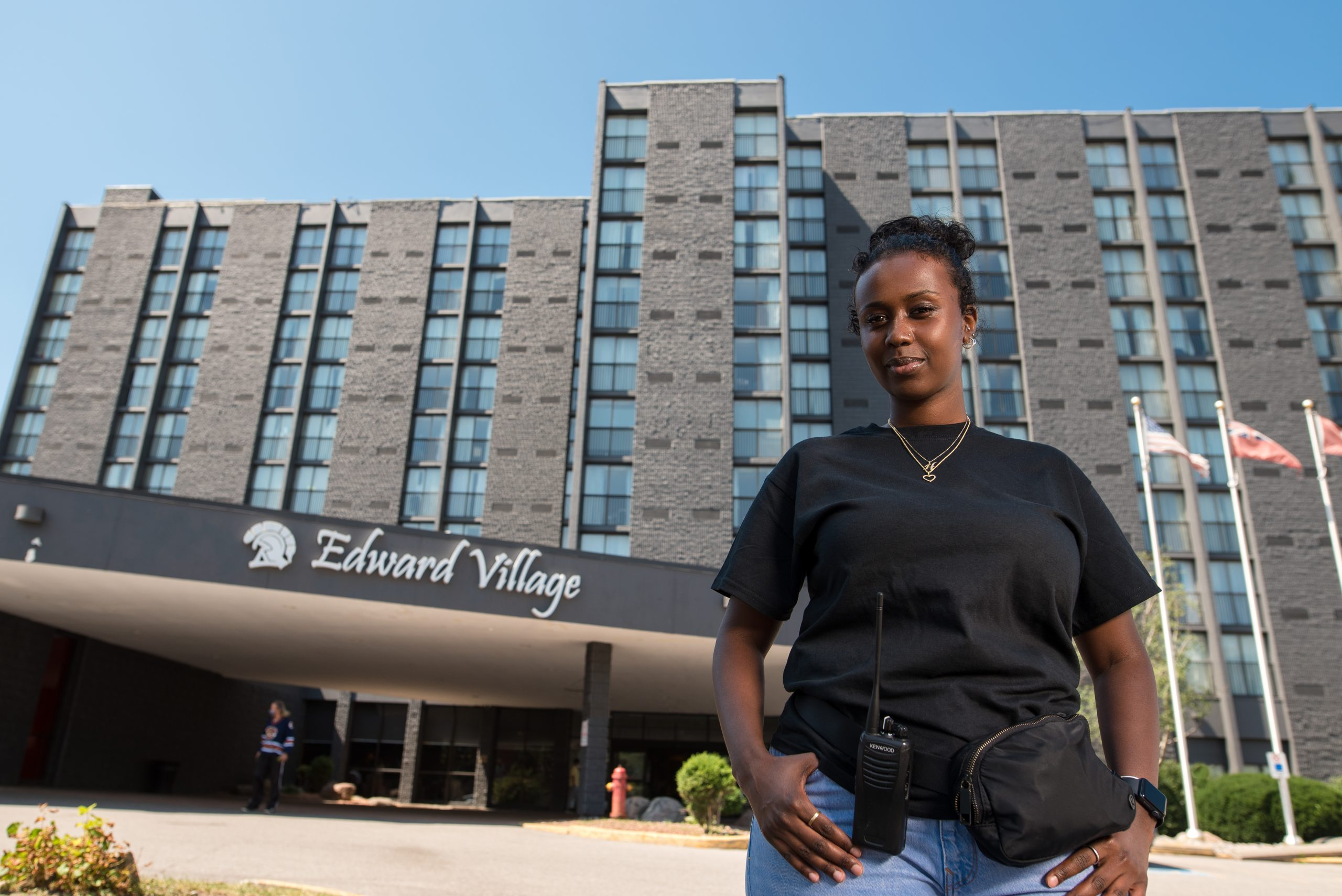 A woman is standing in front of Edward Village Hotel